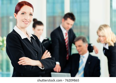 Business - meeting in an office; a colleague is looking into the camera