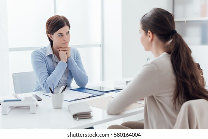Business meeting in the office and job interview: a female executive is meeting the candidate and talking