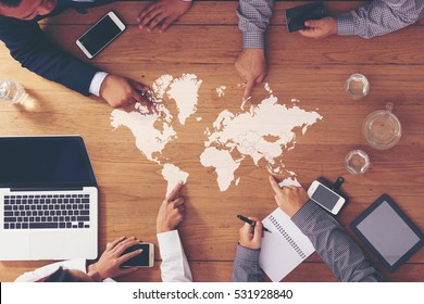 Business meeting on the wooden table.working area. Hand pointing to your message. (World map from NASA)