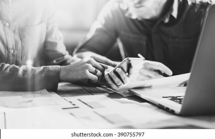 Business meeting picture.Photo young businessmans crew working with new startup project in modern loft.Generic design smartphone holding female hands. Horizontal, film effect, black and white. Blurred