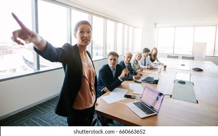 Business meeting and presentation in modern conference room. Asian businesswoman showing something important to colleagues sitting at table.