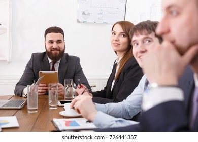 Business meeting, successful team with male bearded boss. Result of work. Office discussion, communication with partners at the desk. Crop