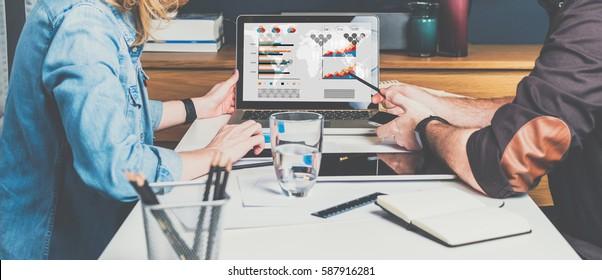 営業会議。チームワーク。ビジネスマンとビジネスマンが、ノートパソコンの前でテーブルに座り、仕事をしている。PCの画面に鉛筆を表示します。 PCの画面にグラフ、グラフ、図を表示します。