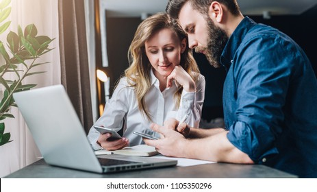 Business meeting. Teamwork. Businesswoman and businessman sitting at table in front of laptop. Man and woman use smartphones. Online education for adult, marketing, distance work, financial planning.