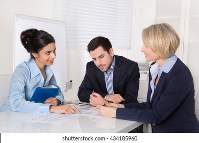 Business meeting. Three people sitting at the table in an office.
