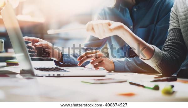 Business meeting time. Photo young account managers crew working with new startup project. Notebook on wood table. Idea presentation, analyze plans. Wide,film effect