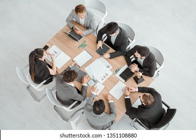 Business meeting. Top view of businessman executive in group meeting with other businessmen and businesswomen in modern office.