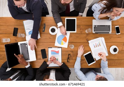 Business meeting top view. Multiethnic people work in office, above view of wooden table