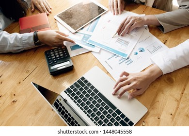 business meeting, business woman Explain analyze the company's sales plan to team leader and business owner by use computer laptop, calculator, stock maket chart on wood desk in conferance.