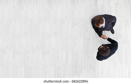 Business men shaking hands, finishing up a meeting, top view with copy space