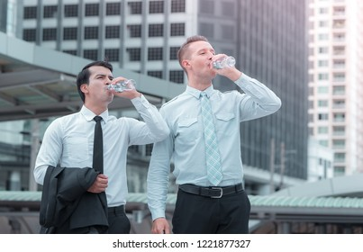 Business men taking a break drinking water on a hot day outdoor