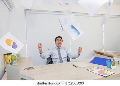 Business men are very happy and laughing to be able to close the project and throw many project papers in his office. Asian business are successful in doing business. Business happy time concept.
