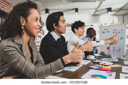 Business men and women of different nationalities give thumbs up happily and smiling. In the meeting room at the office. Concept diversity meeting happy smilling.