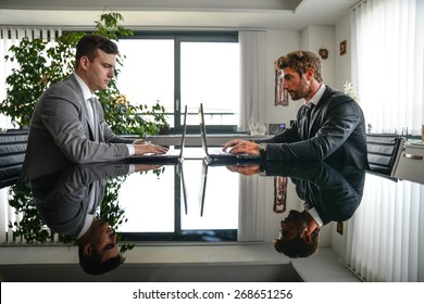 Business men working on computer desk - Busy office workers computing on lap top - Two men sitting at computer desk in front of each others