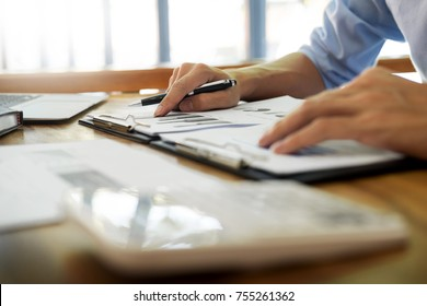 business men working on wooden desk(table) with notebook computer paper, pencil and hand in office, financial concept