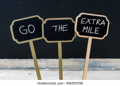 Business message GO THE EXTRA MILE written with chalk on wooden mini blackboard labels, defocused chalkboard and wood table in background