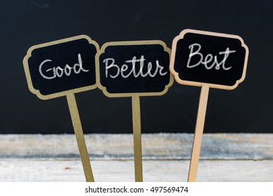 Business message Good, Better, Best written with chalk on wooden mini blackboard labels, defocused chalkboard and wood table in background