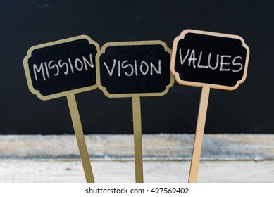 Business message MISSION, VISION, VALUES written with chalk on wooden mini blackboard labels, defocused chalkboard and wood table in background