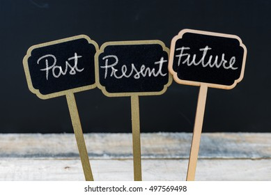 Business message Past, Present, Future written with chalk on wooden mini blackboard labels, defocused chalkboard and wood table in background