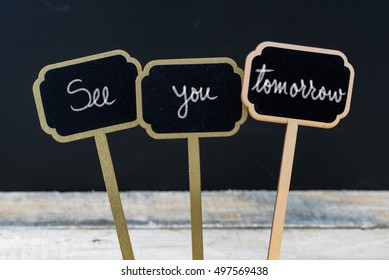 Business message See You Tomorrow written with chalk on wooden mini blackboard labels, defocused chalkboard and wood table in background