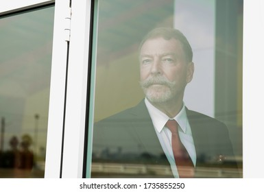Business middle aged man in suit thinking  and looking away by the window searching or waiting for his family, friend or partnership. Home alone. Work form home.Home alone.