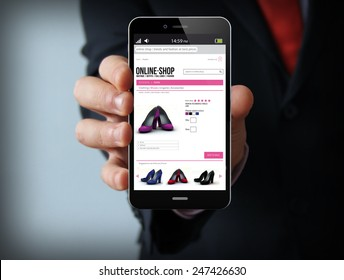 business and mobility communications concept: businessman holding a modern smartphone with online shop