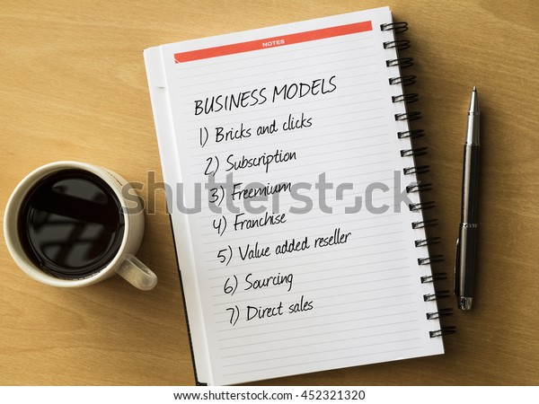 Business models - handwriting on notebook with cup of coffee, business concept.