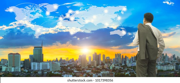Business and modern connection technology concept. Businessman standing on roof top and looking forward to business district center with connection line on world map double exposure on sunset sky.