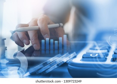 Business modern technology, accounting and finance investment concept. Double exposure of business man working on digital tablet computer and coin with digital diagram, business data, graph interface
