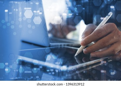 Business, modern technology, IoT concept. Business man working at modern office. Web designer using stylus pen working on digital tablet and laptop computer with technology background. blue tone