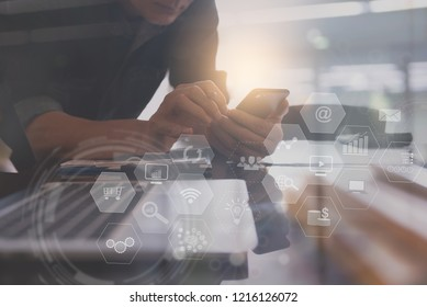 Business modern technology, software development, BI Business Intelligence concept. Businessman using mobile smart phone, working on laptop computer at office with technology icons on virtual screen