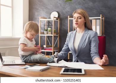 Business mom meditating during working in office while her cute baby playing with toys. Business, motherhood, multitasking and family concept.