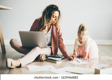 Business mom working with loptop at home while her daughter drawing on the floor. Business, motherhood, multitasking and family concept.