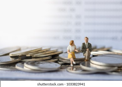 Business and money concept. Businessman and female miniature figure sitting and talking on stack of coins with bank passbook as background.