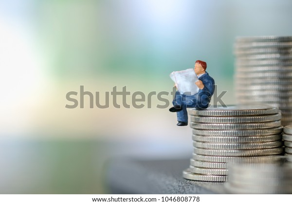 Business and money concept. Businessman miniature figure sitting and reading a newspaper on top of stack of silver coins.