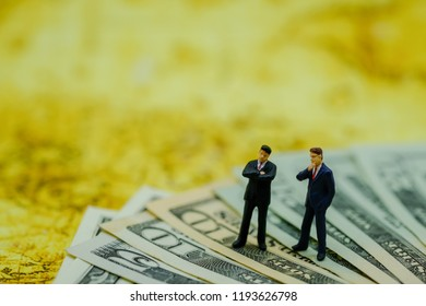 Business and Money concept.  Two businessman miniature figures standing and thinking on US dollar banknotes.