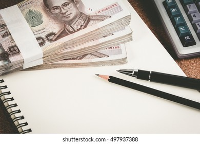 Business money desk concept. Calculator, pen and money on desk with copy space for text. Money calculator pen business on notebook.