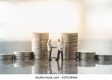 Business, money and financial concept. Two tiny miniature figures of businessman standing and handshake with stack of coins.