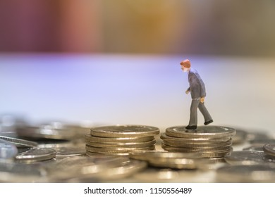 Business Money , saving and planning concept. Businessman miniature figure walking on stack of coins.