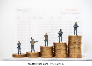 Business, Money Security Concept. Group of special operations soldiers miniature figure people with guns and weapons on top of stack of gold coins on bank passbook.