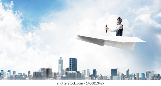 Business motivation concept with pilot sitting in paper airplane. Funny man in aviator hat and goggles driving paper plane above city. Dreaming to fly in sky. Modern megapolis with high buildings.