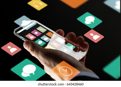 business, multimedia, people and modern technology concept - close up of businessman hand with transparent smartphone with menu icons on screen over black background