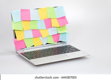 Business multitasking, ideas and organisation concept with colorful sticky notes completely covering an open laptop screen over a white background