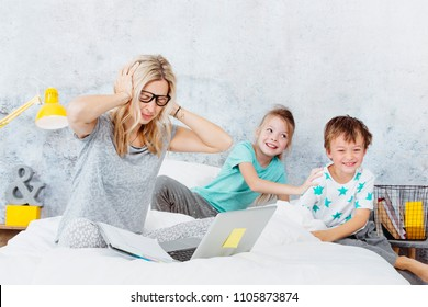 Business mum at work while her kids are playing in bed