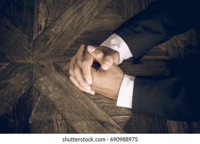 Business negotiation skills with male executive sitting at office desk with confident pose and hands crossed, body language for determination and willpower
