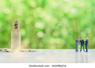 Business negotiation, top management team share vision together : Miniature figurine CEO CFO CMO discuss / talk or brainstorming on company future income / revenue project with dollar bag on coins.