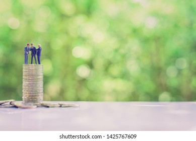 Business negotiation, top management team share vision together : Miniature figurine CEO CFO CMO discuss / talk or brainstorming on company future income / revenue project on top most of the coins.