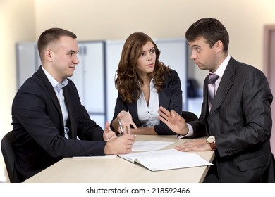 Business negotiations. Salesmen and buyer discuss the contract sitting around the table at the office room.