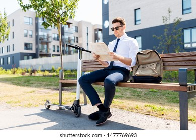 business news and corporate people and concept - young businessman with bag, electric scooter reading newspaper on street bench in city