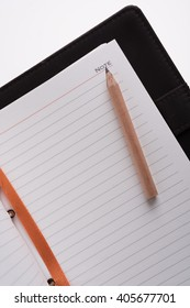 Business notebook and brown pencil background